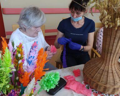 Przy stole siedzi seniorka i terapeutka Anna Rzepczyńska. Obydwie robią palemki z bibuły. Przed nimi na blacie stoi wazon z wielkanocnymi palmami. Palmy wykonane są z kolorowej bibuły, gałązek bazi i bukszpanu. Obok widać wazon z suszonymi kwiatami i źdźbłami