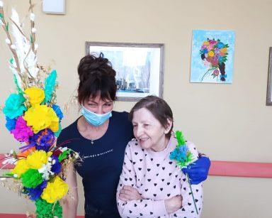 Na korytarzu stoi uśmiechnięta terapeutka Anna Rzepczyńska. Jedną ręką obejmuje stojącą obok seniorkę. W dłoni trzyma palmę z kolorowej bibuły. W drugiej ręce trzyma wysoką palmę z papierowych kwiatów i gałązek bazi