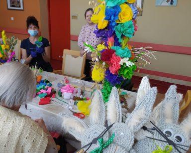 Przy stole siedzi seniorka. Obok niej widać świąteczne dekoracje: wykonane na szydełku kolorowe kwiaty i zające z włóczki. Na blacie widać kolorowe wielkanocne palmy. Po drugiej stronie stołu stoi seniorka. Niedaleko niej siedzi terapeutka Anna Rzepczyńska