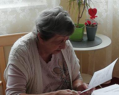 Przy stole siedzi seniorka. W rękach trzyma i czyta propozycje standardów, które mają obowiązywać. Przed nią na blacie leżą teksty zapisane różnymi sposobami