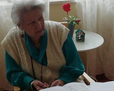 Przy stole siedzi seniorka i słucha wypowiedzi innych uczestników. Przed nią na blacie leżą kolorowe kartki i kartki z tekstem