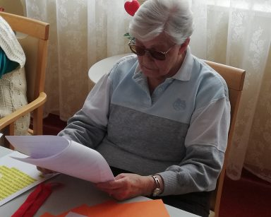 Przy stole siedzi seniorka i czyta materiały dotyczące tematu spotkania, czyli tekstu łatwego do czytania. Przed nią na blacie leżą teksty zapisane różnymi sposobami