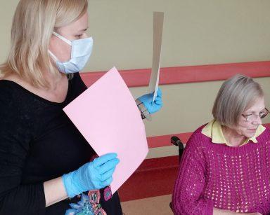 Neurologopedka Anna Szmaja-Wysocka prezentuje w jaki sposób kolor ma wpływ na czytelność tekstu. W jednej ręce trzyma różową kartkę, a w drugiej beżową kartkę. Obok niej siedzi seniorka i przegląda rozłożone na stole materiały