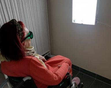 Na białej ścianie wisi włączona prostokątna lampa antydepresyjna. Przed nią na wózku inwalidzkim siedzi seniorka i korzysta z fototerapii. Ma założone okulary ochronne