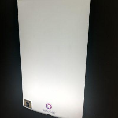 Na ciemnej ścianie wisi prostokątna lampa antydepresyjna. Lampa jest włączona. Wytwarza światło imitujące światło słoneczne