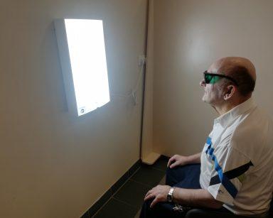 Na białej ścianie wisi włączona prostokątna lampa antydepresyjna. Przed nią na krześle siedzi senior i korzysta z fototerapii. Ma założone okulary ochronne