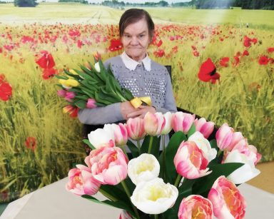 Na pierwszym planie widać stolik nakryty kremowym obrusem. Na blacie stoi wazon z białymi i różowymi tulipanami. Za stolikiem siedzi uśmiechnięta seniorka. W rękach trzyma bukiet żółtych, pomarańczowych, białych i różowych tulipanów. Seniorka siedzi na tle fototapety przedstawiającej słoneczny dzień na polu z jasnozielonym zbożem i czerwonymi makami