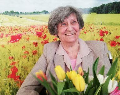 Na pierwszym planie widać uśmiechniętą seniorkę. W rękach trzyma bukiet żółtych, pomarańczowych, białych i różowych tulipanów. Seniorka siedzi na tle fototapety przedstawiającej słoneczny dzień na polu z jasnozielonym zbożem i czerwonymi makami