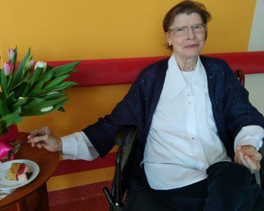 Przy stoliku siedzi uśmiechnięta seniorka. Na blacie stoi wazon z białymi i różowymi tulipanami. Obok na białym talerzyku leży kawałek ciasta