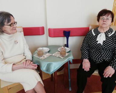 Przy stoliku siedzą dwie odświętnie ubrane seniorki. Na stole stoją dwie szklanki z kawą i dwa białe talerzyki z ciastem