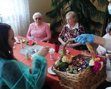 Przy stole siedzi makijażystka Marta. Pani dyrektor Agnieszka Cysewska częstuje ją czekoladowymi pralinami, które znajdują się w wiklinowym koszu. Z drugiej strony stołu siedzą dwie seniorki i rozmawiają ze sobą. Stół nakryty jest czerwonym obrusem. Na blacie znajdują się kubki z kawą, talerzyki z ciastem, wazon z różowym kwiatem