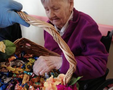 Na pierwszym planie widać przystrojony pomarańczowymi i różowymi kwiatami wiklinowy kosz. Kosz jest pełen pralin i czekoladowych cukierków. Seniorka, która siedzi na przeciwko częstuje się cukierkiem