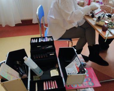 Na pierwszym planie widać rozłożony kuferek wyłożony czarnym materiałem. W kuferku znajdują się akcesoria i kosmetyki do robienia makijażu. W tle widać jak makijażystka Monika siedzi przy stoliku i zajmuje się pielęgnacją dłoni seniorki. Na blacie poustawiane są akcesoria i kosmetyki do pielęgnacji oraz kolorowe lakiery do paznokci