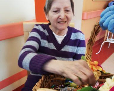 Na krześle siedzi uśmiechnięta seniorka. Sięga ręką do wiklinowego kosza. Kosz jest przystrojony białymi, pomarańczowymi i różowymi kwiatami. W środku widać czekoladowe cukierki i pralinki