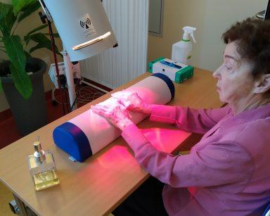 Na krześle, przy stoliku siedzi seniorka. Ręce trzyma na podłużnej poduszce położonej na blacie stolika. Na jej dłonie pada czerwone rozgrzewające światło z lampy solux