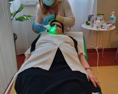 Na kozetce leży seniorka. Jej oczy przykrywają czarne okulary ochronne. Przy jej głowie siedzi dyrektor Agnieszka Cysewska, na twarzy ma maseczkę, a na rękach niebieskie nitrylowe rękawiczki. Za pomocą specjalnego urządzenia wykonuje seniorce masaż twarzy z użyciem zielonego światła. To zabieg neutralizująco-kojący i likwidujący obrzęki. W tle widać biały stolik. Na blacie leżą środki do dezynfekcji, pudełko z nitrylowymi rękawiczkami i kosmetyki pielęgnacyjne