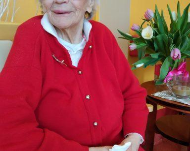 Na krześle siedzi uśmiechnięta seniorka. Za nią widać drewniany, okrągły stolik. Na blacie stoi szklanka z kawą oraz wazon z białymi i różowymi tulipanami