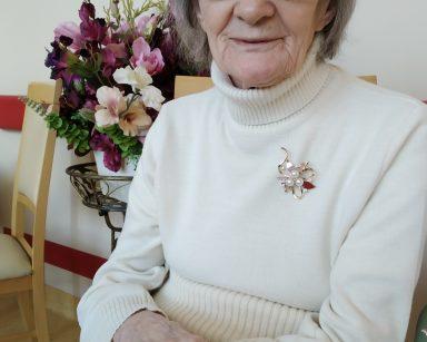 Na krześle siedzi uśmiechnięta seniorka. W tle widać dekoracje z fioletowych, różowych i kremowych kwiatów