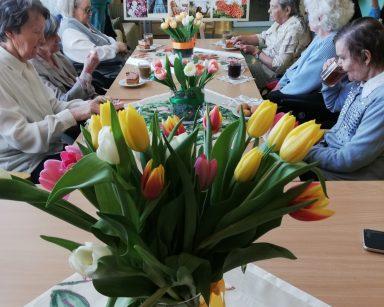 Na pierwszym planie widać wazon stojący na stole. Wazon jest pełen różowych, pomarańczowych, żółtych i białych tulipanów. Po obu stronach stołu siedzą seniorki. Przed nimi stoją szklanki z kawą, talerzyki z kawałkami ciasta i wazony z tulipanami. Obok stoi Kierownik Działu Terapeutyczno-Opiekuńczego Mariola Ludwicka i Pani Edyta Życzyńska. W tle widać tablicę udekorowaną zdjęciami kobiet i kwiatów