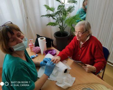 Przy stoliku siedzi seniorka. Kierownik Działu Medyczno-Rehabilitacyjnego Ewa Siłakiewicz-Witt zajmuje się pielęgnacją jej dłoni. Na blacie stołu widać papierowy ręcznik i kosmetyki do manicure