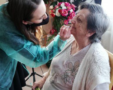 Makijażystka Marta pochyla się nad seniorką. W ręce trzyma konturówkę, którą maluje jej usta. Seniorka siedzi na krześle. W ręku trzyma trzy różowe tulipany. W tle widać dekorację: czarno-białe zdjęcie Marilyn Monroe oraz bukiety różowych, czerwonych, białych i kremowych kwiatów