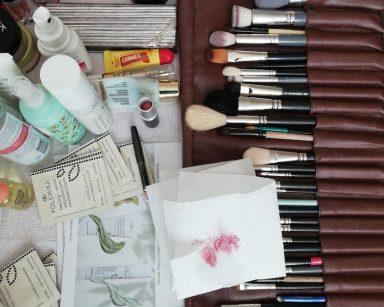 Widok z góry. Na stoliku leży rozłożone skórzane etui z pędzlami do makijażu. Obok stoją buteleczki z kosmetykami do pielęgnacji i malowania