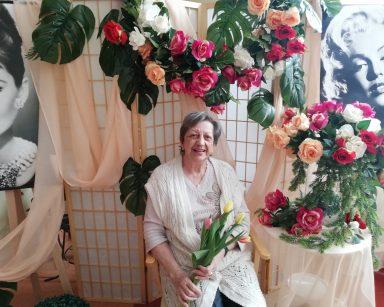 Przy stoliku siedzi uśmiechnięta seniorka. W rękach trzyma bukiet żółtych, pomarańczowych, białych i różowych tulipanów. Za nią wisi girlanda kolorowych kwiatów. Obok na stoliku stoi dekoracja z czerwonych, białych, różowych kwiatów i zielonych gałązek