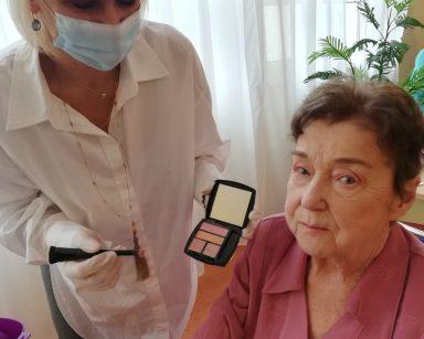 Na krześle siedzi seniorka. Nad nią pochyla się makijażystka Monika. W jednej ręce trzyma dwustronny pędzelek do nakładania cieni, a w drugiej otwarte pudełko z lusterkiem i cieniami do makijażu