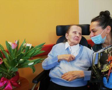 W czarnym fotelu siedzi seniorka. Obok niej na drewnianym stoliku stoi wazon z różowymi i białymi tulipanami. Z drugiej strony nachyla się nad nią terapeutka Magdalena Poraj-Górska i pokazuje artykuł w gazecie