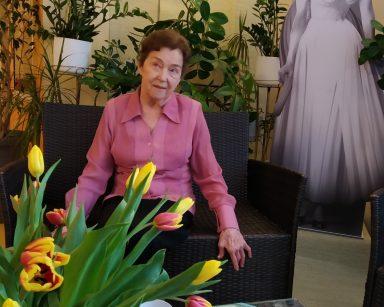 Na rattanowym fotelu siedzi seniorka. Przed nią stoi stolik z wazonem pełnym tulipanów, białym dzbankiem i białymi filiżankami. W tle widać kącik z zielonymi roślinami oraz pełnowymiarową czarno-białą tekturową postać przedstawiającą Ritę Hayworth