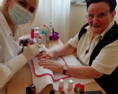 Przy stoliku siedzą roześmiane dwie panie: seniorka i makijażystka Monika. Na stoliku znajdują się przybory do manicuru i lakiery do paznokci