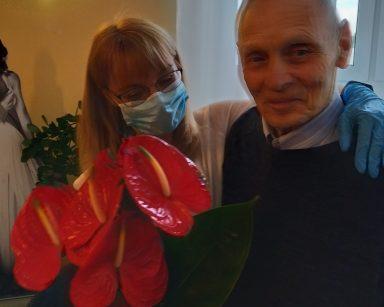 Na rattanowym siedzisku siedzą: uśmiechnięci senior i dyrektor Agnieszka Cysewska. Pani Dyrektor jedna ręką obejmuje seniora, w drugiej trzyma bukiet kwiatów, które od niego dostała. Bukiet składa się z czerwonych kwiatów anturium
