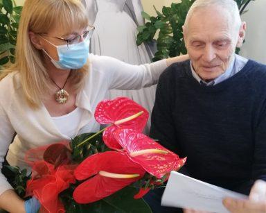 Na rattanowym siedzisku siedzą uśmiechnięci: senior i dyrektor Agnieszka Cysewska. Pani Dyrektor jedna ręką obejmuje seniora, w drugiej trzyma bukiet kwiatów, które od niego dostała. Bukiet składa się z czerwonych kwiatów anturium. Senior wręcza jej kartkę z życzeniami