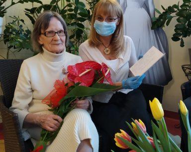 Na rattanowym siedzisku siedzą odświętnie ubrane seniorka i dyrektor Agnieszka Cysewska. Panie uśmiechają się. Seniorka na kolanach trzyma bukiet czerwonych kwiatów anturium. Pani dyrektor ma w rękach kartkę z życzeniami