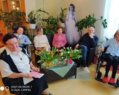 Na pierwszym planie widać niski rattanowy stolik. Na jego blacie leży satynowy obrus i stoją dwa wazony pełne białych, żółtych, różowych, pomarańczowych tulipanów. Wokół siedzi pięć seniorek i jeden senior. W tle widać zielone kwiaty i czarno-białą tekturową postać Rity Hayworth