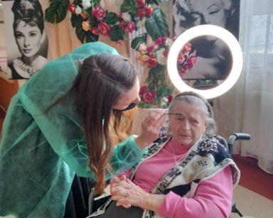 Makijażystka Marta pochyla się nad siedzącą seniorką. W ręku trzyma szczoteczkę, którą układa jej brwi. W tle widać lampę do makijażu, udekorowaną kwiatami ścianę, czarno-białe zdjęcia Marilyn Monroe i Audrey Hepburn