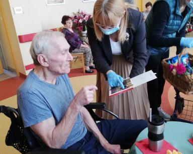 Dyrektor Agnieszka Cysewska trzyma w rękach pudełko czekoladek i nachyla się nad seniorem. Senior siedzi na wózku i wyciąga rękę by poczęstować się czekoladką. Obok stoi stolik z kawą i kawałkami pomarańczy na talerzyku. W tle widać pracowników i mieszkańców Domu