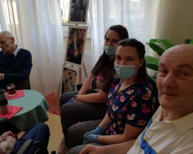 Na tle w okna, na rattanowym siedzisku, siedzą senior, fizjoterapeutka Martyna Józefczyk i fizjoterapeutka Paulina Winczura. Obok przy stoliku siedzą częściowo widoczni dwaj seniorzy
