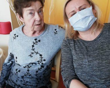 Obok siebie siedzą uśmiechnięte seniorka i neurologopedka Anna Szmaja-Wysocka. Seniorka obejmuje ją ręką