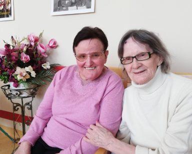 Na krzesłach siedzą dwie seniorki. Obie się uśmiechają. W tle widać bukiet z różowych, kremowych i fioletowych kwiatów