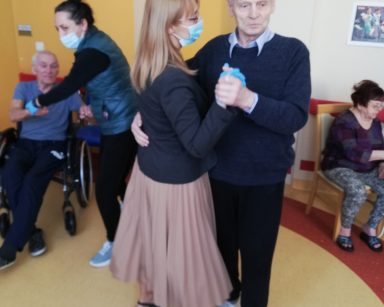 Na pierwszym planie widać dyrektor Agnieszkę Cysewską tańczącą z seniorem. W tle widać terapeutkę Magdalenę Poraj-Górską, która tańczy z seniorem siedzącym na wózku