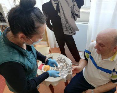 Terapeutka Magdalena Poraj-Górska nachyla się nad seniorem. W rękach trzyma pocztówki z życzeniami. Senior wyciąga rękę po pocztówkę. W tle widać stolik ze szklanką kawy i talerzykiem z cząstkami pomarańczy oraz fragment czarno-białej tekturowej postaci