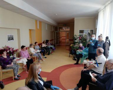 Terapeutka Magdalena Poraj-Górska stoi przy oknie i odczytuje życzenia dla Panów. Na korytarzu siedzą seniorzy, seniorki oraz pracownicy i słuchają życzeń