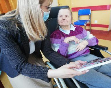 Dyrektor Agnieszka Cysewska pochyla się nad seniorką. W rękach trzyma kolorowe czasopismo i wskazuje znajdujące się w nim zdjęcie. Seniorka siedzi w specjalistycznym czarnym wózku. Ma uniesioną głowę i słucha pani dyrektor
