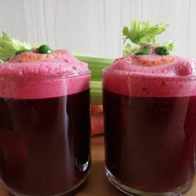 Na pierwszym planie widać z bliska dwie szklanki z sokiem. Sok ma kolor buraczkowy, z wierzchu widać dekorację: różową piankę i zielone łodygi selera. W tle leżą pomarańczowe marchewki i zielony seler naciowy