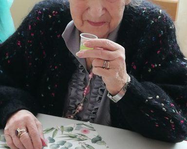 Uśmiechnięta seniorka siedzi przy stole. W ręce trzyma kieliszek z jasnozielonym sokiem. Przed nią na białym blacie widać rozłożoną serwetkę z wzorem w różowe kwiaty i zielone liście. Obok stoi pusty kieliszek po soku