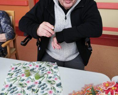 Przy stole siedzi senior. Przed nim na blacie są rozłożone serwetki w różowe kwiaty i zielone liście. Na serwetce stoją dwa przezroczyste kieliszki z sokami, pierwszy sok od lewej jest jasnozielony, drugi ciemnozielony. Obok na blacie widać wykonaną szydełkiem serwetkę. Na niej stoi wazon pełen zrobionych szydełkiem kolorowych kwiatów: żółtych, pomarańczowych, różowych, czerwonych. Każdy z kwiatów ma w środku żółty koralik, a rant wykończony na biało. Serwetkę i kwiaty zrobiła mieszkanka naszego Domu - Pani Zofia