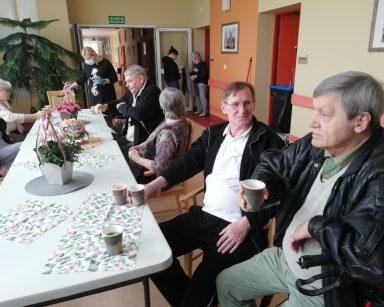 Przy stole siedzą seniorzy. Stół jest udekorowany serwetkami o kwiatowym wzorze oraz bukietami kwiatów. Po lewej stronie stołu siedzą dwie seniorki. U szczytu stoi neurologopedka Anna Szmaja-Wysocka. Koło niej po prawej stronie stołu siedzi senior, a następnie seniorka. W dalszej kolejności widać dwóch siedzących seniorów pogrążonych w rozmowie