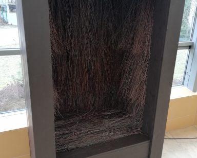 Na tle okna stoi tężnia solankowa wysoka na dwa metry. Zbudowana jest z drewna w kolorze palisander (ciemny brąz). Przez wycięty na jej przedniej ścianie prostokątny otwór widać brązowe gałązki brzozowe