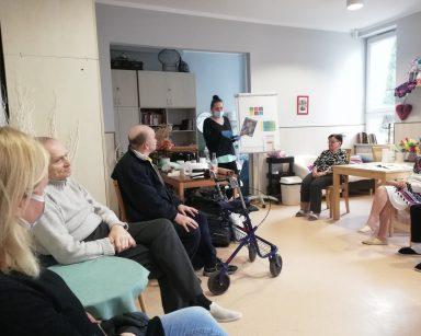 Na środku pokoju stoi terapeutka Magdalena Poraj-Górska i opowiada o Światowym Dniu Recyklingu. W tle widać białą tablicę flipchart. Po prawej stronie Pani Magdy siedzi dwóch seniorów i neurologopedka Anna Szmaja-Wysocka. Po jej lewej stronie siedzą trzy seniorki. Wszyscy słuchają Pani terapeutki